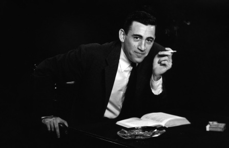 """NEW YORK - NOVEMBER 20, 1952: *** EXCLUSIVE - CALL FOR IMAGE *** JD Salinger poses for a portrait as he reads from his classic American novel """"The Catcher in the Rye"""" on November 20, 1952 in the Brooklyn borough of New York City. Salinger died on January 27, 2010. (Photo by Antony Di Gesu/San Diego Historical Society/Hulton Archive Collection/Getty Images)"""